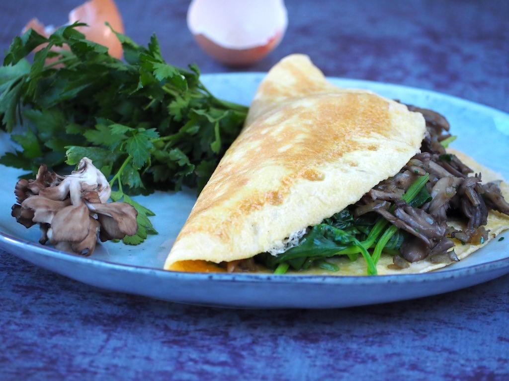 Goed gevulde omelet met paddenstoelen en spinazie